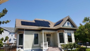 Small Victorian house with solar panels on different parts of sloped roof